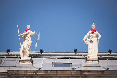 cityhall: Statues on the roof of the city hall of Bayonne with a red scarf during the Summer festival (Fetes de Bayonne), France