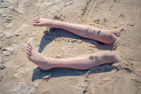 Legs of a boy buried in the sand of a beach, vintage style