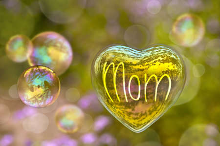 Word Mom written on a soap bubble in the shape of heart, mothers day concept