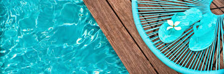 Turquoise blue garden chair and flip flopson on the edge of a swimming pool, panoramic view