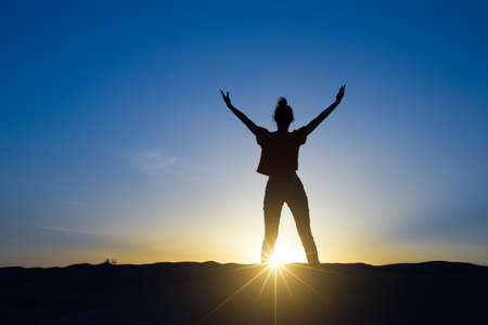 Silhouette of a woman standing in the sunlight with the arms up