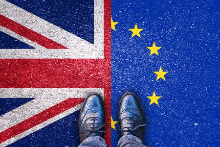 Brexit, vlaggen van het Verenigd Koninkrijk en de Europese Unie op asfaltweg met benen