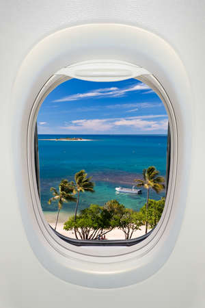 beach window: Window of an airplane from inside, view on a tropical beach and sea