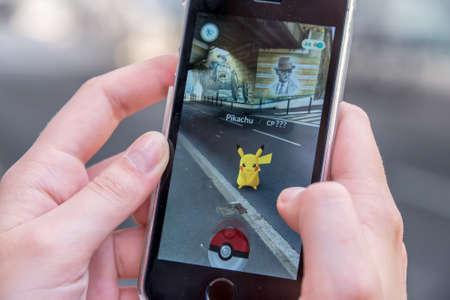 CHAVILLE, FRANCE - JULY 24: Apple iPhone5s with Pikachu from Pokemon Go application, hands of a teenager playing on the first day of the launching of the game in France 에디토리얼