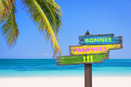 Bonnes vacances (meaning happy summer) on direction signs, beach and palm tree background Banque d'images