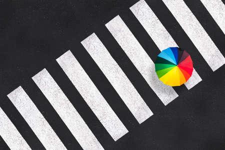 Top view of a rainbow umbrella on a pedestrian crosswalk Standard-Bild
