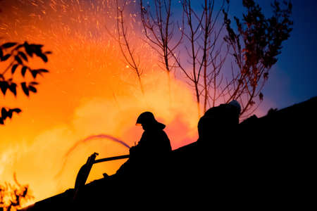burning house: Silhouettes of firemen on the roof of a burning house Stock Photo