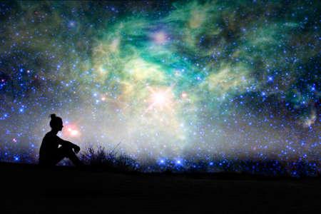 Silueta ženy sedí venku, hvězdné noci pozadí