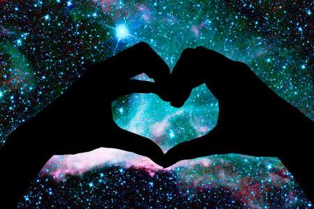 Handen in de vorm van een hart, sterrennachtachtergrond
