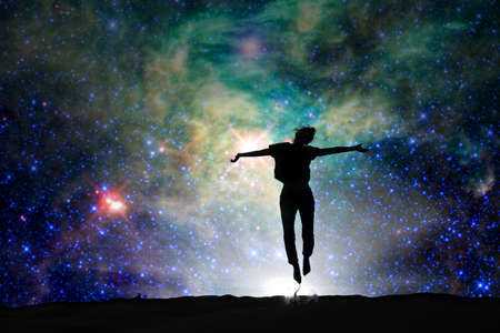 Silhouette of a woman jumping, starry night background