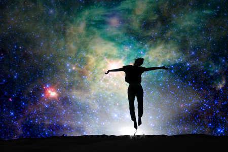 Silhouette kobiety skoków, gwiaździste noc tle