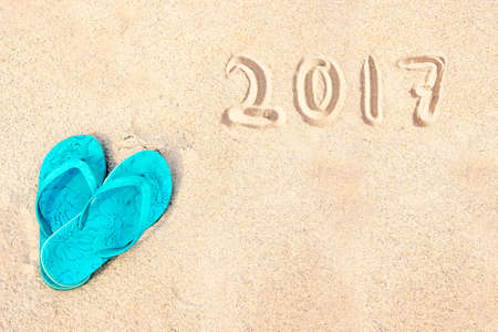 Blue pair of flip flops on the beach, 2017 written in the sand