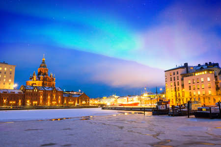 Northern lights over the frozen Old Port in Katajanokka district with Uspenski Orthodox Cathedral in Helsinki, Finland 스톡 콘텐츠