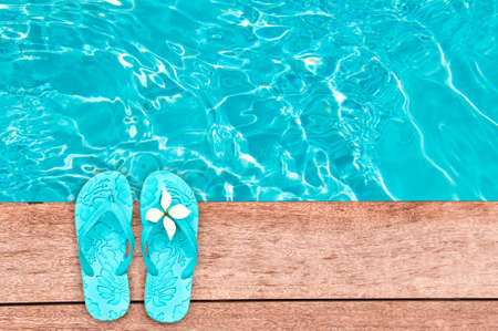 pool deck: Sandals by a swimming pool, summer concept Stock Photo
