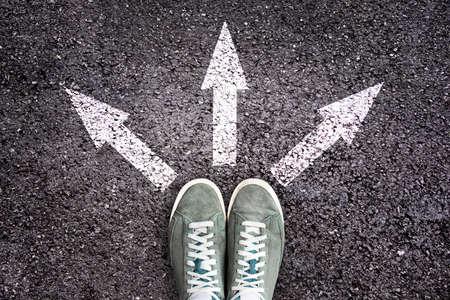 Schoenen en pijlen wijzen in verschillende richtingen op asfaltvloer