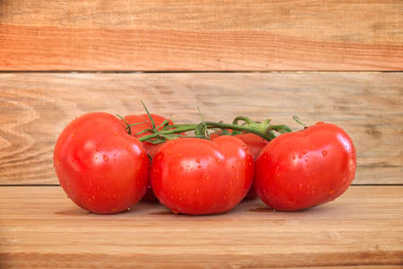 trickles: Branch of tomatoes with water droplets on wooden planks background