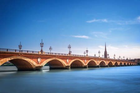 Pont de Pierre bridge with St Michel cathedral, Bordeaux, France