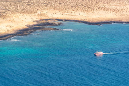 Aerial view of a boat in the ocean with the coastline of La Graciose island in Lanzarote, Canary islands, Spain
