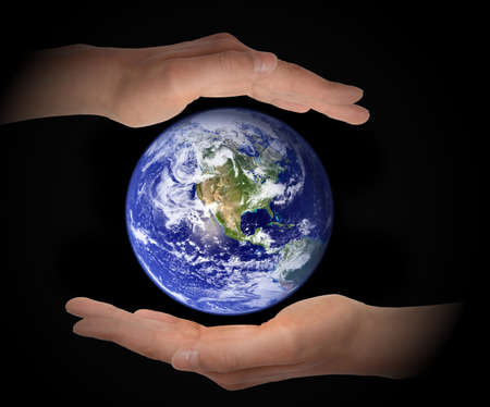 Glowing earth globe in hands on black background, environment concept - elements of this image furnished by NASA