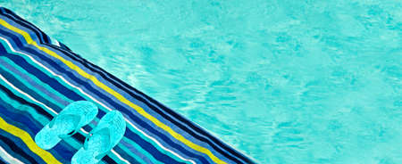 Swimming pool, bath towel and flip flops, panoramic background, summer concept