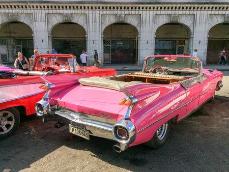HAVANA, CUBA - APRIL 18: Tourists admiring vintage american classic cars parked in Havana, on April 18, 2016 in Havana