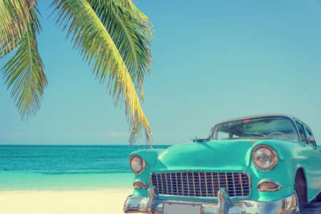 Classic car on a tropical beach with palm tree, vintage process Imagens