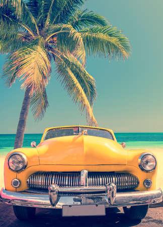 Voiture classique sur une plage tropicale avec palmier, processus vintage Banque d'images