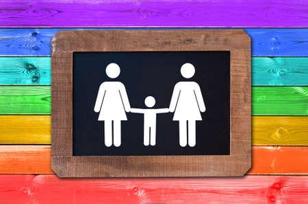 Familia lesbiana con el signo blanco del niño en una pizarra, fondo de los tablones de madera de la bandera gay del arco iris Foto de archivo