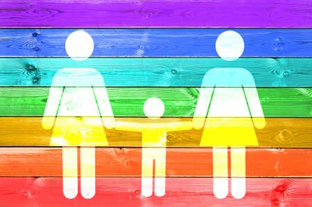 Famiglia lesbica con il segno bianco del bambino su un fondo di legno delle plance della bandiera gay dell'arcobaleno