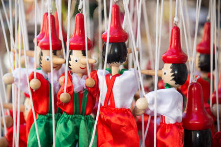 Traditional painted red and green wooden Pinocchio marionette dolls, Italy