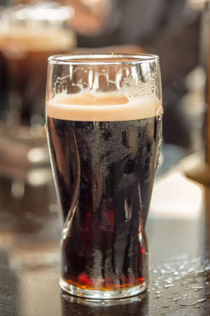 Close up of a glass of stout beer on a bar counter Stock Photo