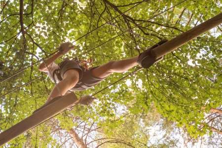 Teenager having fun on high ropes course, adventure, park, climbing trees in a forest in summer