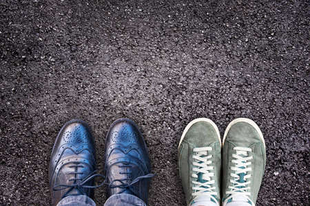 aging face: Sneakers and business shoes side by side on asphalt, work life balance concept Stock Photo