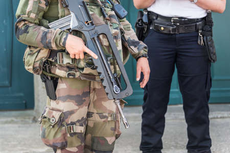 Close up of a French soldier with an automatic riffle, policeman in the background, security and emergency state concept