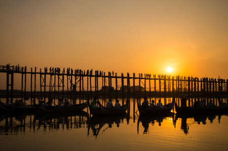Silhouettes of tourists in boats admiring U Bein bridge over the Taungthaman Lake at sunset, in Amarapura, Mandalay, Myanmar Stock Photo