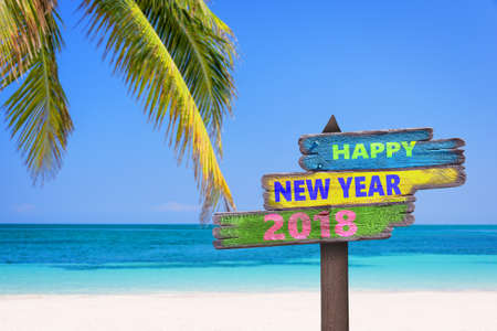 Hapy new year 2018 on a colored wooden direction signs, beach and palm tree background Stock fotó