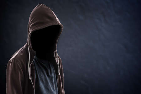 Silhouette of man with a hood and face in the dark, black background with copy space, criminal or hacker concept Reklamní fotografie