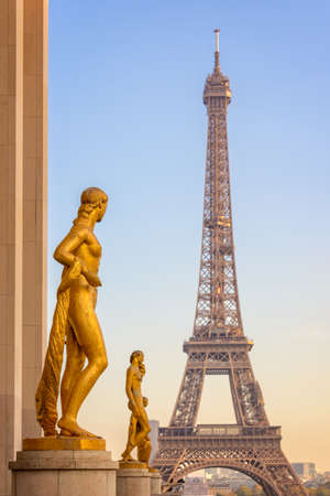 Golden bronze statues on Trocadero square, Eiffel tower in the background, Paris France Stock Photo