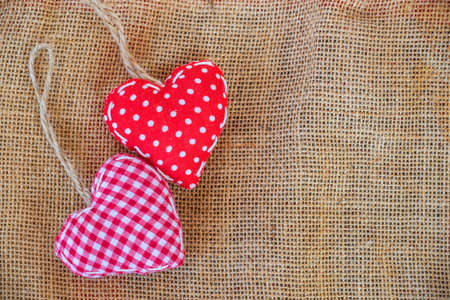 Two red fabric hearts on rustic canvas background