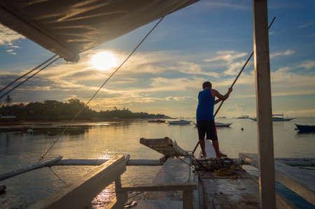 Fisherman on a banka, traditional filipino fishing boat at sunset, Cebu island, The Philippines