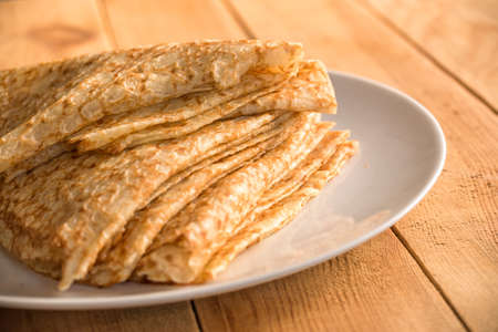 Close up on a stack of folded crepes (french pancakes) on a plate, wooden background