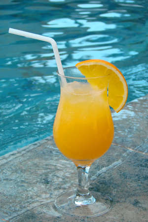 Glass of orange juice with a straw by a swimming pool