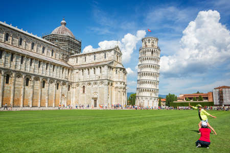 People having fun and taking pictures of the leaning tower of Pisa in Tuscany, Italy