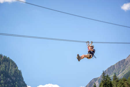 Teenager having fun on a zip line in the Alps, adventure, climbing, via ferrata during active vacations in summer Stock Photo