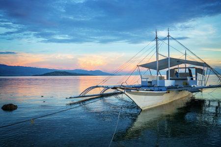 Banka, traditional filipino fishing boat at sunset, Cebu island, The Philippines