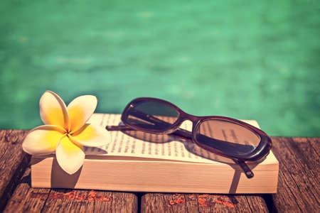 Book and sunglasses, blue water background, vintage process