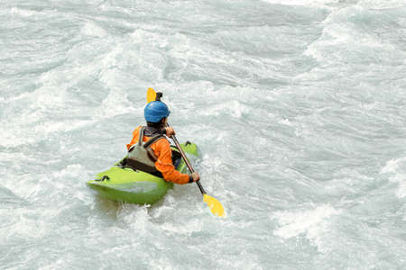 Kayaker paddling in white water rapids,  with copy space