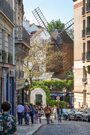 People walking in Lepic street, view on the famous Moulin de Galette on the hill of Montmartre in Paris France Editorial