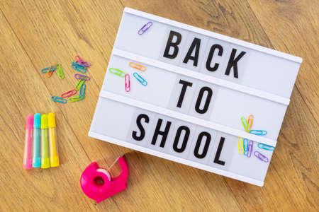 Back to school written on a modern light box on wood background, colorful supplies Standard-Bild