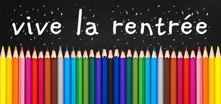 Vive la rentree (meaning Back to school) written on black chalkboard background with colorful wooden pencils